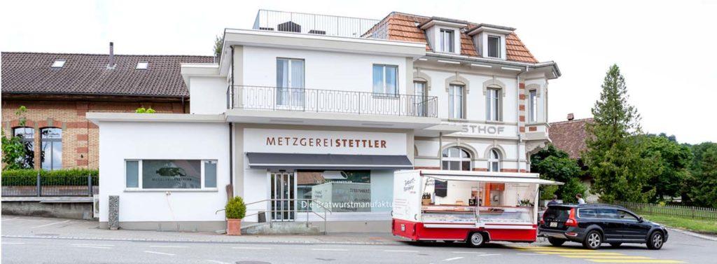 Aussenaufnahme der Metzgerei Stettler in Schüpfen mit dem Märit Bern Verkaufanhänger und dem Zugfahrzeug Volvo.